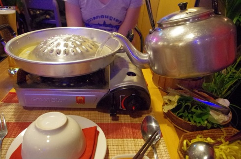 Adding soup to the hot pot while the grill gets hot on top.  Noodles and veggies can be seen on the side