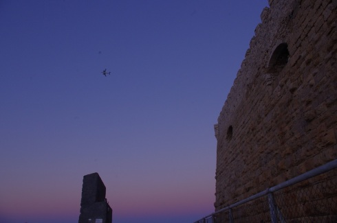An ancient wall and an airplane above